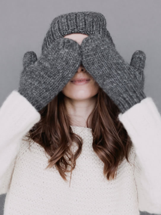 Girl with hat and gloves hiding face